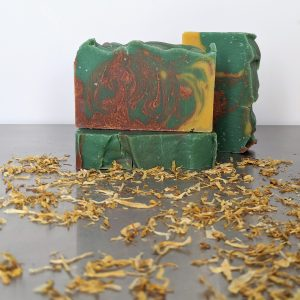 three bars of organic handmade fall leaves organic soap colored with green clay and calendula petals in a hanger swirl pattern with greens reds and yellows using essential oils of clove, eucalyptus and cedarwood for glowing skin