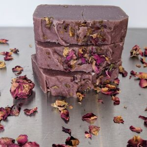 three bars of organic handmade soap colored with rosehip powder and rose petals scented with mulled cider fragrance a deep burgundy plum color from beet juice with essential oils of orange patchouli and ylang ylang