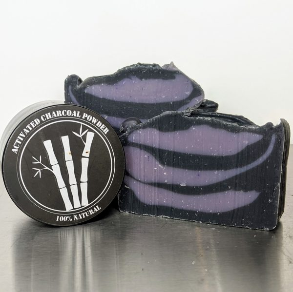 handmade, organic soap with activated charcoal powder to cleanse pores and detoxify skin, two bars of soap with container of activated charcoal, soap has purple and black swirls, scented with essential oils of lavender, bay and clove