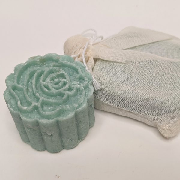 green shampoo bar with second shampoo bar in compostable muslin packaging